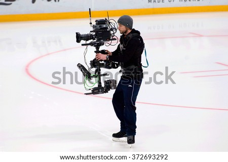 MOSCOW - JANUARY 29, 2016: Unidentified reporter with camera filming a hockey game Sweden vs Czech on League of World legends of Ice hockey championship in VTB ice arena, Russia. Czech won 8:2 - stock photo