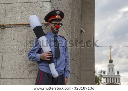 "MOSCOW,31 JULY,2015: A clown in the form of a policeman standing with his rod near main entrance to the All-Russia Exhibition Centre during the street theater festival ""Inspiration"" in Moscow,Russia - stock photo"