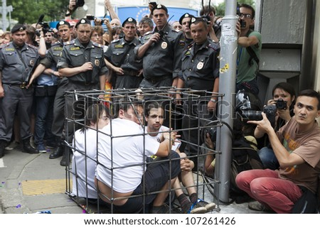 MOSCOW - JULY 4. Supporters of female Russian punk band Pussy Riot sit locked inside mock defendants cage outside court to support musicians during hearings on  Pussy Riot case, on July 4, 2012, - stock photo