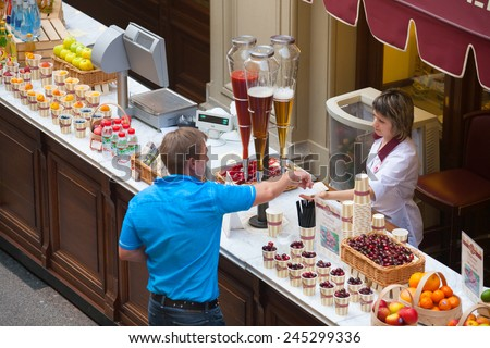 MOSCOW - JULY 29: The buyer pays the money to the seller of fruit and soft drinks in the GUM store on July 29, 2014 in Moscow. - stock photo
