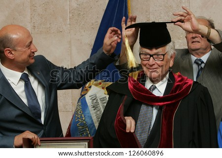 MOSCOW - JUNE 7: French designer Pierre Cardin is helped to put on Doctor's traditional outfit at the Moscow State University of Design and Technology June 7, 2011 in Moscow, Russia.