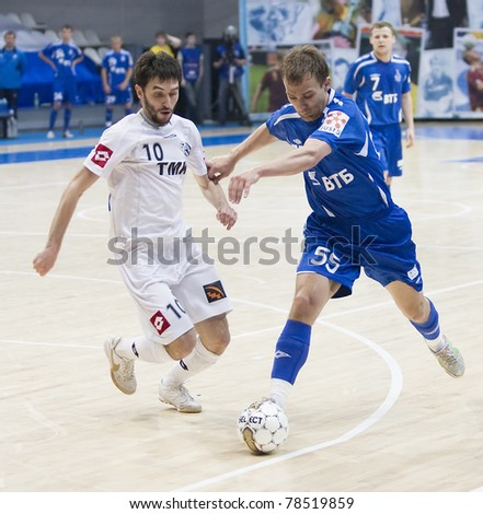 MOSCOW - JUNE 2, Russian Futsal championship, play-off games Dinamo vs. Sinara, final on June 2, 2011 in Moscow. Badretdinov (Dinamo) is trying to tackle a ball from his opponent - stock photo