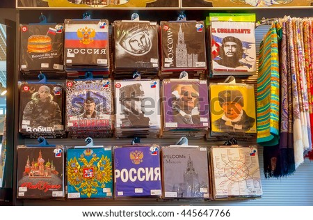 MOSCOW - JUNE 11, 2016: Souvenir t-shirts with Putin and russian symbols in the shop window in International Airport. Duty-free shop.  Russia and Strong Russians in russian letters on t-shirts. - stock photo
