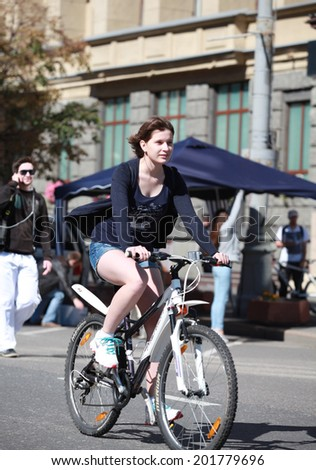 """MOSCOW - JUNE 29: Unidentified people ride bicycles at the Third Moscow bicycle parade held under the slogan: """"City needed bicycle infrastructure!"""". Taken on June 29, 2014 in Moscow. - stock photo"""