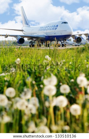 MOSCOW - MAY 22:  Airplane of Transaero airlines at Domodedovo airport, view from low angle through dandelion, May 22, 2012, Moscow, Russia. Domodedovo  - largest and most modern airport in Russia.