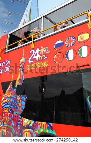 MOSCOW - MAY 01, 2015: Red double-decker, touristic bus in Moscow, on the Red Square. Saint Basils church is painted on the bus. Flags of dirrefent countries.