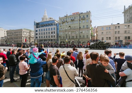 MOSCOW-MAY 9, 2015: Victory parade dedicated to the 70th anniversary of the Soviet victory over Germany. People on the streets of Moscow greeted Pass technique. Organization of view of the parade for - stock photo