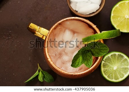 Moscow Mule in a copper mug - Vodka drink served with mint garnish and lime wedge, selective focus, top down view - stock photo