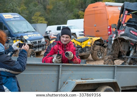"MOSCOW-OCTOBER 10: A man shows a broken part of the car on the 5 stage of the XSR-MOTO.RU Cross Country in Moscow, Park ""Velyaminovo""; on October 10, 2015 - stock photo"