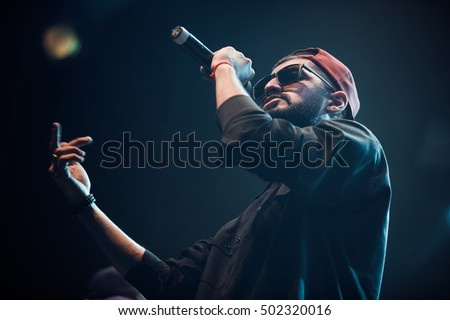 MOSCOW-20 OCTOBER,2016: Cool rap singer Miyagi sing on stage of night club.Hip hop music performer singing in microphone on scene.Rapper in bright concert lighting.Portrait of singer with mic on stage