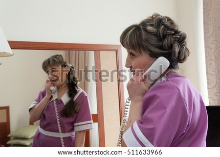 MOSCOW - OCTOBER 31: Maid girl, dressed in purple, speaking by phone at room in Izmaylovo hotel on October 31, 2016 in Moscow. Izmailovo is four-building hotel located in Izmaylovo District of Moscow.
