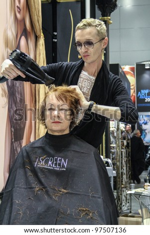 MOSCOW - OCTOBER 26: Professional hairdresser works at the international exhibition of professional cosmetics and beauty salon equipment INTERCHARM on October 26, 2011 in Moscow