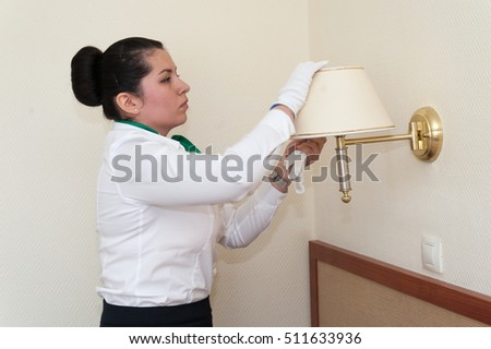 MOSCOW - OCTOBER 31: Supervisor girl, dressed in white and black, checking cleanliness of lamp at room in Izmaylovo hotel on October 31, 2016 in Moscow. Izmailovo is four-building hotel in Moscow.