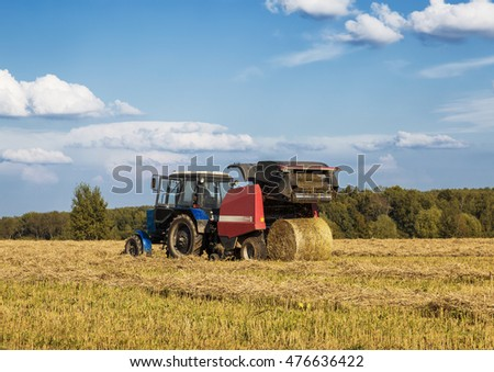 MOSCOW REGION, RUSSIA - AUGUST 21, 2016: harvesting hay in a field on a summer day