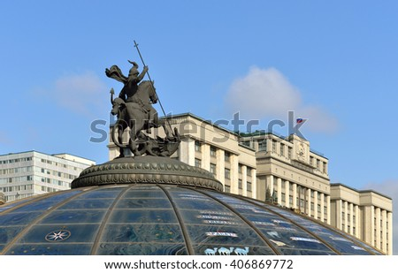 MOSCOW, RUSSIA - APRIL 4, 2016:Manege Square and Monument on a glass cupola to Saint George and the Dragon, patron of Moscow against background of State Duma and Russian Federation flag