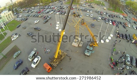 MOSCOW, RUSSIA - APRIL 2, 2014: Workers on crane construct star monument near parking with lot of cars at evening, aerial view
