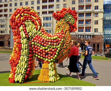 MOSCOW, RUSSIA - AUG 14,2015: Holiday jam marks start of harvest time in middle Russia. Main alley of Fruit Vernissage fair is adorned with 2-metre high fruit figurines, installations by Moscow artists. - stock photo