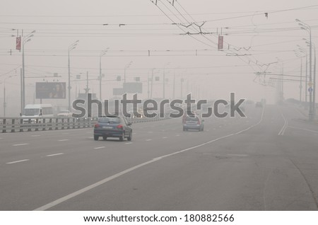 MOSCOW, RUSSIA - AUGUST 7, 2010: Cars run down Krestovsky Bridge in thick smog caused by wildfires - stock photo