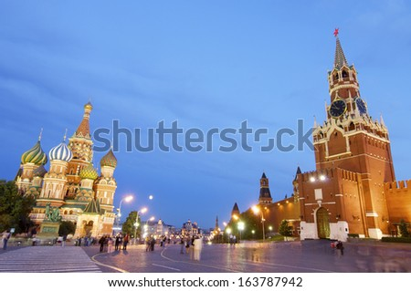 MOSCOW, RUSSIA - AUGUST 3: Night on August 3, 2009 in Moscow: Tourists walking on the Red Square, distinguished St. Basil Cathedral and Kremlin. - stock photo