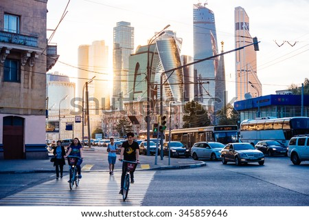 MOSCOW, RUSSIA - AUGUST 18, 2015: People are riding bicycles at Kutuzovsky avenue in front of skyscrapers of Moscow City international business centre in Moscow, Russia. - stock photo