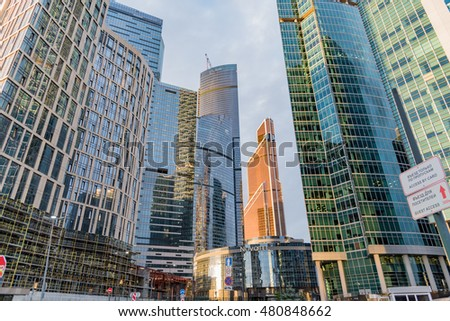MOSCOW, RUSSIA - AUGUST 17, 2016 -  workers on the roof. Futuristic buildings in Moscow City. Front view to high modern skyscrapers.