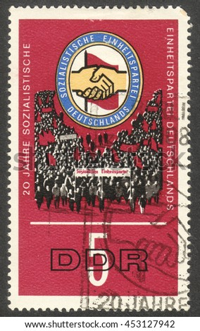 "MOSCOW, RUSSIA - CIRCA JULY, 2016: a stamp printed in DDR shows Insignia of the Socialist Unity Party, the series ""The 20th Anniversary of the Socialist Unity Party"", circa 1966 - stock photo"