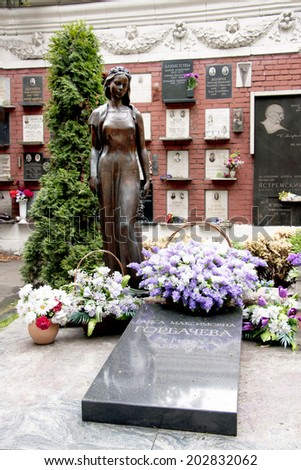 MOSCOW, RUSSIA - CIRCA SEPTEMBER, 2010: Last resting place of Raisa Gorbachev-Titarenko at the Novodevichy National cemetery in Moscow. Black tomb slab with bronze statue of a mourning young woman.  - stock photo