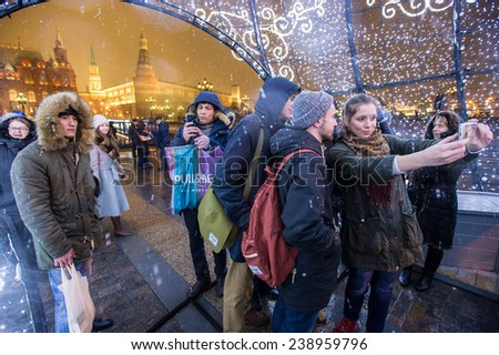 MOSCOW, RUSSIA - DECEMBER 19: Muscovites and guests from central asia take a photo on Manezhnaya Square decorated for New Year  celebration on December 19, 2014 in Moscow, Russia. - stock photo