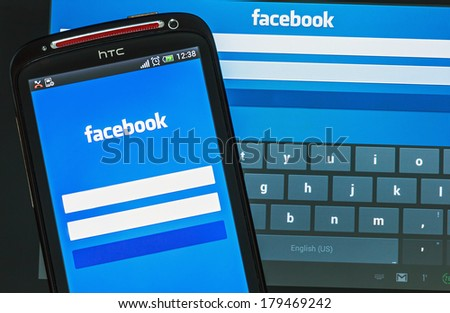 Moscow, Russia - February 27, 2014: Entrance to the social network facebook via mobile phone HTC. The biggest social network in the world. Was founded in 2004 by Mark Zuckerberg. - stock photo