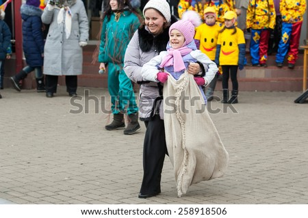 MOSCOW, RUSSIA - FEBRUARY 22: Unidentified woman and girl on running sack competition on Russian religious and folk holiday Maslenitsa near Culture center Peresvet on February 22, 2015, Russia - stock photo