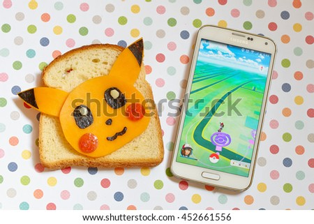 Moscow, Russia - July 15, 2016 Editorial image: Smartphone with Pokemon Go application and Fan Art Pikachu Sandwich - stock photo