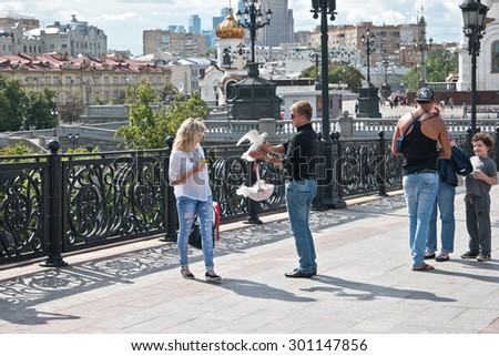 MOSCOW, RUSSIA - July 22.2015: Man-photographer offers to the girl to be photographed with hand pigeons - stock photo