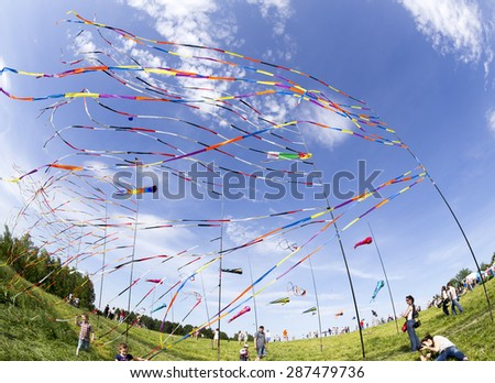 MOSCOW, RUSSIA - JUN 1: Fluttering in the wind colorful ribbons and colorful kites at the festival of kites with happy people and children around  on Jun 1, 2014 in Moscow, Russia. - stock photo