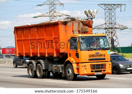 MOSCOW, RUSSIA - JUNE 2, 2012: Orange Ford Cargo gabage truck at the city street. - stock photo