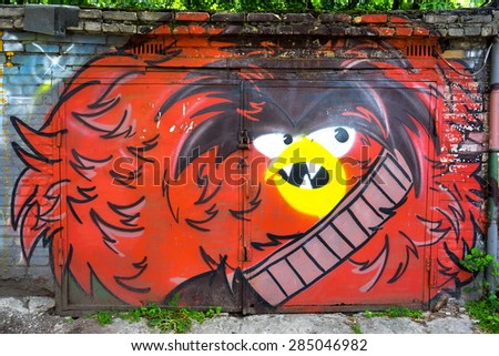 MOSCOW, RUSSIA - JUNE 06, 2015: Street art or graffiti by unidentified artist in the garage doors. The image of angry red bird. - stock photo