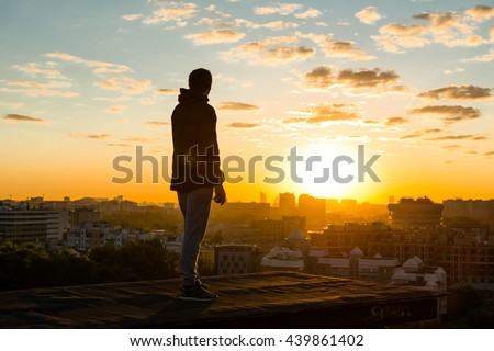 MOSCOW, RUSSIA - JUNE 13, 2016: Young and brave man staying on the edge of high roof in summer during dawn