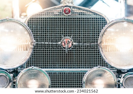 Moscow, Russia - March 3, 2013: Close up view of the silver chrome headlights and grille of a vintage American cadillac with the badge and logo, symmetrical composition. - stock photo