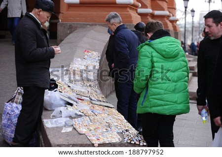 MOSCOW, RUSSIA - MARCH 23, 2014: People buying soviet military medals and badges at the entrance of Red Square in Moscow