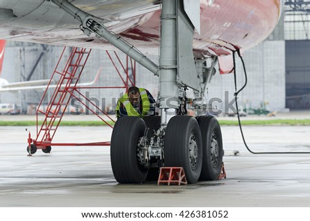 MOSCOW, RUSSIA - MAY 19, 2016: Aircraft  Tupolev-204 Red Wings airline in the parking lot of the international airport Domodedovo. The service engineer carry out work on inspection of the landing gear - stock photo