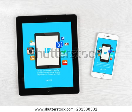 Moscow, Russia - May 25, 2015: Apple iPhone 6 and iPad over table displaying IFTTT application. IFTTT is a web-based service that allows users to create chains of simple conditional statements. - stock photo