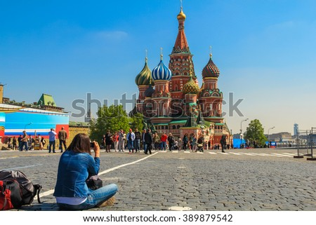 MOSCOW, RUSSIA - MAY 10, 2012 - Girl photographing the Saint Basil's Cathedral. The Cathedral of Vasily the Blessed, commonly known as Saint Basil's Cathedral, is a church in Red Square in Moscow, - stock photo
