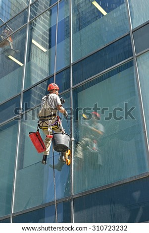 MOSCOW, RUSSIA - MAY 25, 2015: Group of workers cleaning windows service of modern office building in Moscow International Business Center