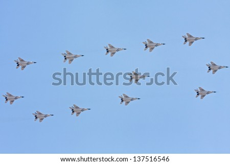 MOSCOW/RUSSIA - MAY 9: 12 Mikoyan MiG-29 (Fulcrum) jet fighter aircrafts form figure 6 against blue sky background on parade devoted to 65th anniversary of Victory Day on May 9, 2010 in Moscow. - stock photo