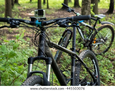Moscow, Russia - May 29, 2016: Mountain bicycles with GoPro 3+ BE action camera mounted on handlebar in the forest