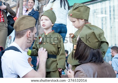 MOSCOW, RUSSIA - MAY 09, 2014: Parents with their children during march of 'Immortal Regiment'. Kids are wearing military uniform - stock photo