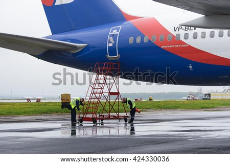 MOSCOW, RUSSIA - MAY 19, 2016: Service engineers mounted the stairs near airplane Azur Air Airline Boeing 757-200. - stock photo