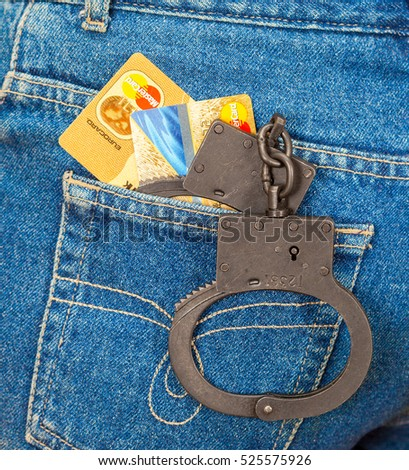 MOSCOW, RUSSIA - NOVEMBER 27, 2016: Black metal handcuffs and credit cards in back jeans pocket