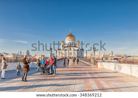 MOSCOW, RUSSIA - NOVEMBER 28, 2015: People are photographed on the Patriarshy Bridge near  Cathedral of Christ the Savior. It is Cathedral of the Russian Orthodox Church