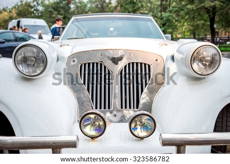 Moscow, Russia - October 2, 2015: Wedding white limo closeup. Some wedding guests standing near the car.