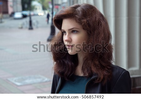 MOSCOW, RUSSIA - SEPTEMBER 17, 2016: Autumn street outdoor closeup portrait of beautiful brunette young woman at the Old Arbat street.